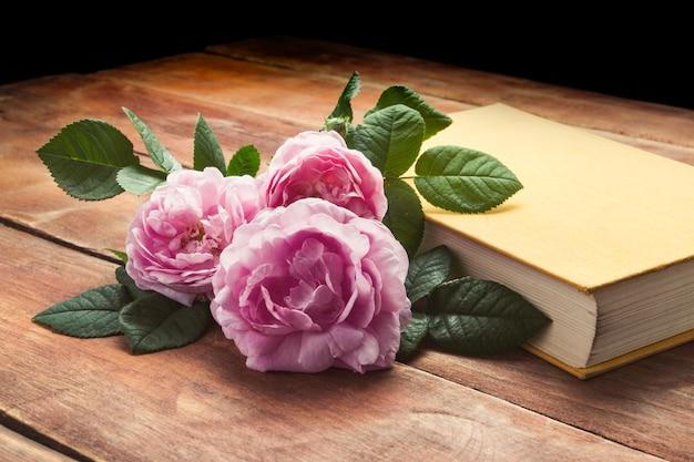 Roses roses et livre avec une couverture jaune sur une surface en bois
