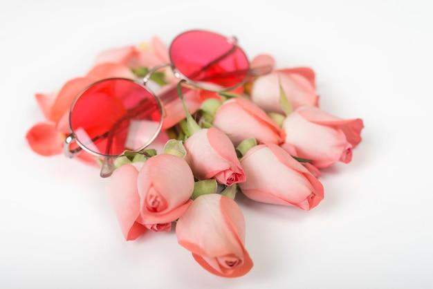Roses roses avec des lunettes de soleil sur la table