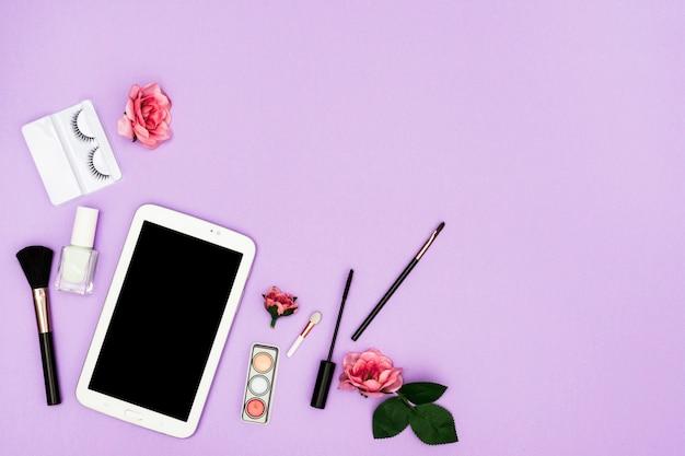 Roses roses avec pinceaux tablette numérique et maquillage sur fond violet
