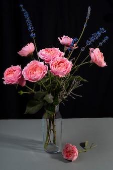 Roses roses pivoine dans un vase en verre sur fond sombre