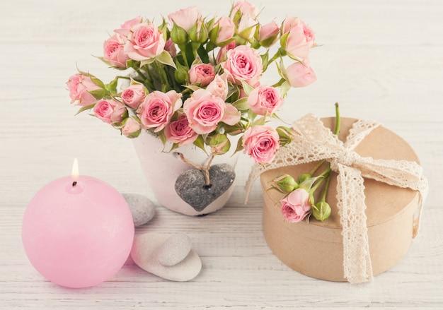 Roses roses en pot de béton avec bougie