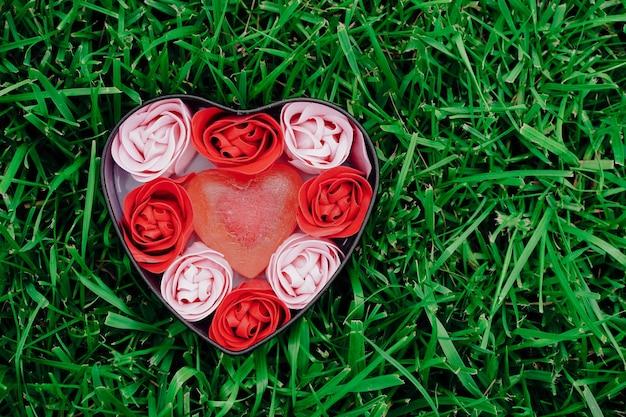 Roses roses et rouges lumineuses faites de copeaux de savon avec des coeurs sur l'herbe verte dans une boîte en forme de coeur valentines espace copie romantique mather day