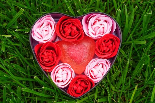 Roses roses et rouges vives faites de copeaux de savon avec des coeurs sur l'herbe verte dans une boîte en forme de coeur vale...