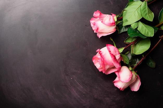 Roses roses sur un tableau noir. joyeuse journée de la femme. concept de la saint-valentin. cadeau pour elle