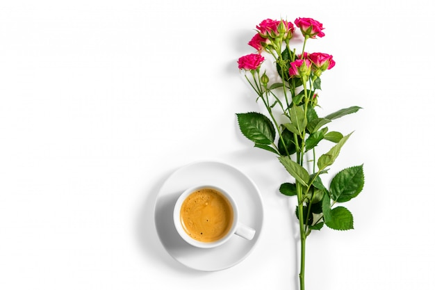 Roses roses avec une tasse de café isolé sur fond blanc