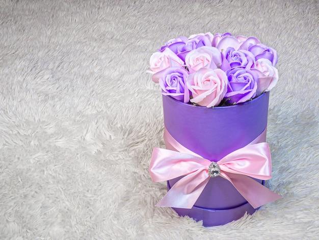 Roses roses et violettes dans une boîte cylindrique violette attachée avec un ruban de soie rose sur fond de fourrure blanche. cadeau romantique délicat pour anniversaire, fête de la femme, mariage et saint-valentin.