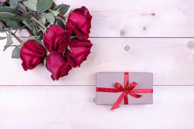 Des roses rouges et une boîte-cadeau attachée avec un ruban