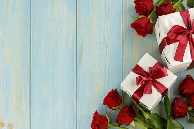 Roses rouges et boîte-cadeau sur une table en bois bleu clair, vue de dessus