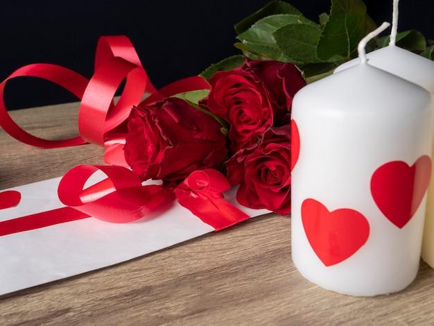 Roses rouges avec bougies et carte blanche avec ruban sur table