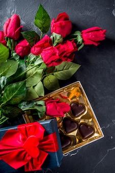 Roses rouges et coeurs en chocolat sur sol en marbre