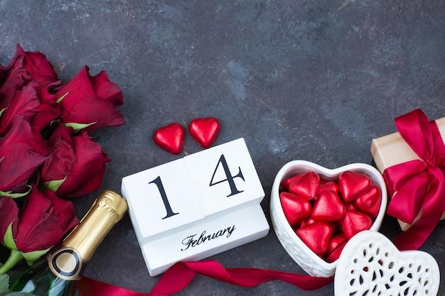 Roses rouges, coeurs rouges, bonbons en forme de cœur, une bouteille de champagne, un cadeau dans une boîte