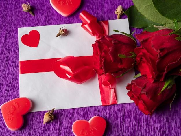 Roses rouges coeurs rouges à côté de boutons de rose et carte avec ruban sur fond violet