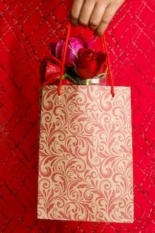 Roses rouges et coffret cadeau sur fond blanc.