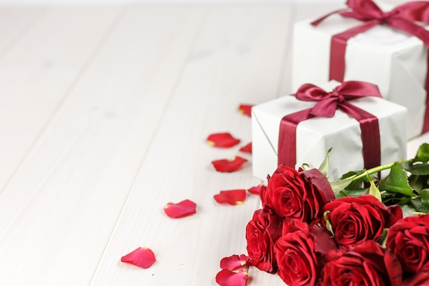 Roses rouges et coffret cadeau sur table en bois blanc