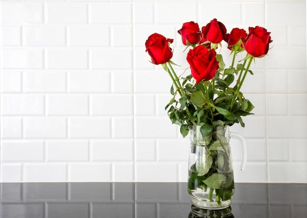 Roses rouges dans un pichet en verre