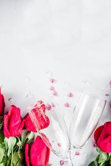 Roses rouges avec deux verres de champagne