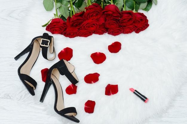 Roses rouges sur fourrure blanche, chaussures noires, rouge à lèvres et pétales de rose.