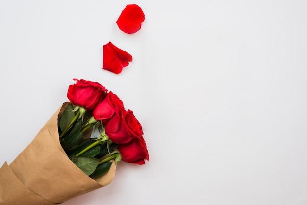 Des roses rouges et des pétales façonnent des ornements sur une surface blanche