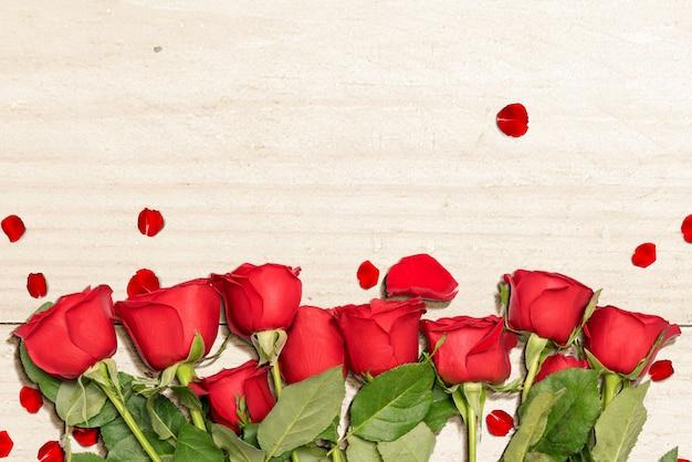 Roses rouges et pétales de rose sur une table en bois