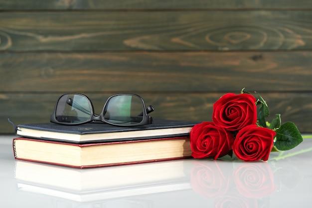 Roses rouges sur table et livre avec espace copie, fond de la saint-valentin avec des roses rouges