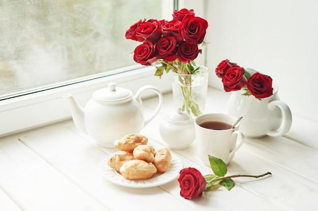 Roses rouges, thé et croissants sur une table près de la fenêtre, petit-déjeuner romantique pour la saint-valentin