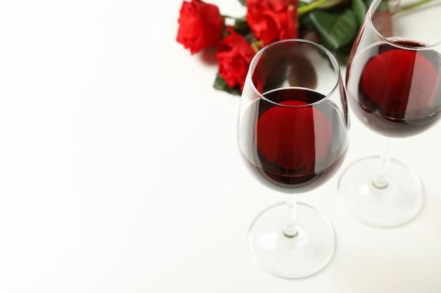 Roses rouges et verres de vin sur fond blanc, espace pour le texte