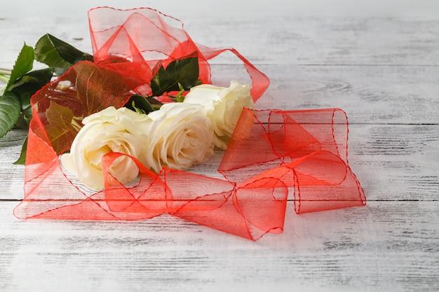 Roses et rubans sur planche de bois, fond de la saint-valentin, jour du mariage
