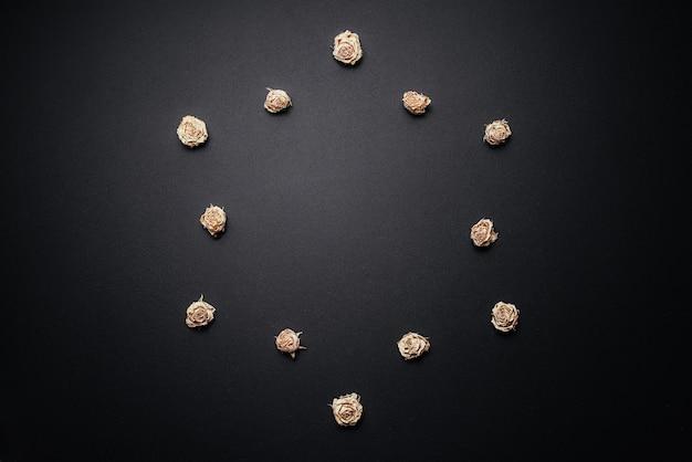 Roses séchées disposées en cercle sur un fond en bois noir.