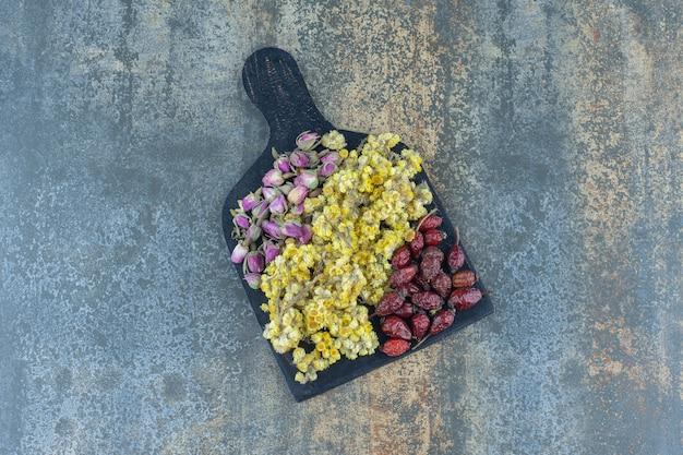 Roses séchées, marguerites et églantier sur planche de bois.