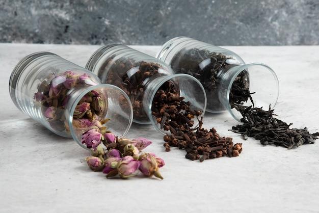Roses séchées avec des thés en vrac sur gris.