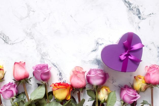 Roses violettes et jaunes, boîte présente sur fond blanc