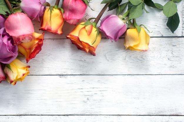 Roses violettes et jaunes, boîte présente sur un fond en bois blanc