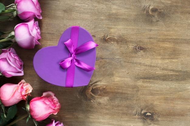 Roses violettes et jaunes, boîte présente sur fond en bois