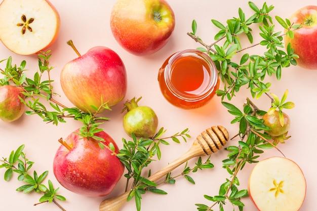 Rosh hashana, concept de vacances du nouvel an juif avec symboles traditionnels, pommes, miel, grenade sur une table rose pastel, abricot. fond plat