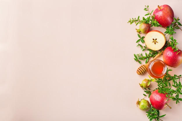 Rosh hashana, concept de vacances du nouvel an juif avec symboles traditionnels, pommes, miel, grenade sur une table rose pastel, abricot. mise à plat, copiez l'arrière-plan de l'espace