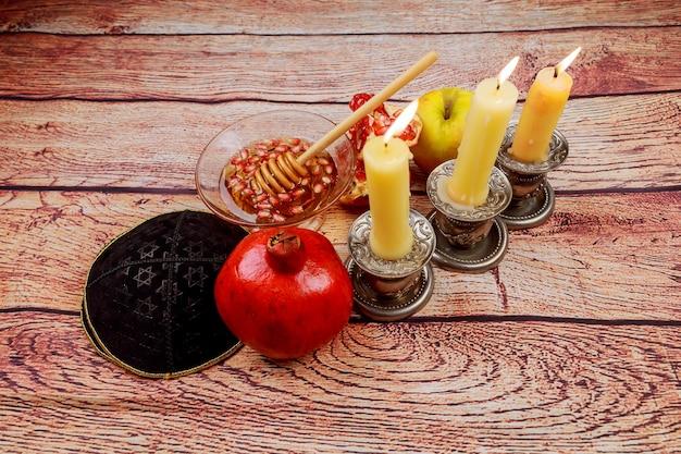 Rosh hashanah jewesh concept de vacances livre de la torah, miel, pomme et grenade sur table en bois. symboles de vacances traditionnels.