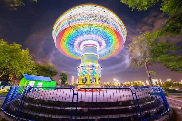 Rotation illuminée attraction grande roue et carrousel manège le soir de l'été dans le parc d'attractions de la ville.