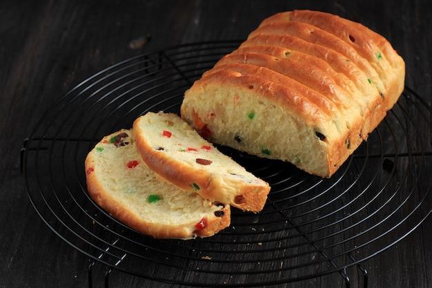 Roti sisir fruité, pain blanc aux fruits secs et raisins pour pâtisserie de noël. sur une grille, isolé sur noir