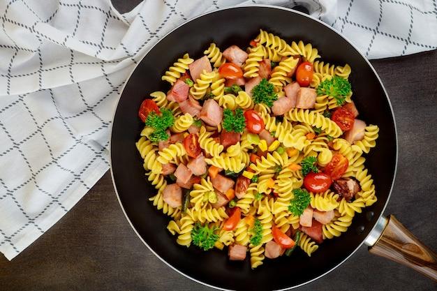 Rotini de pâtes colorées, tomates cerises et jambon sur la poêle. fermer. vue de dessus.