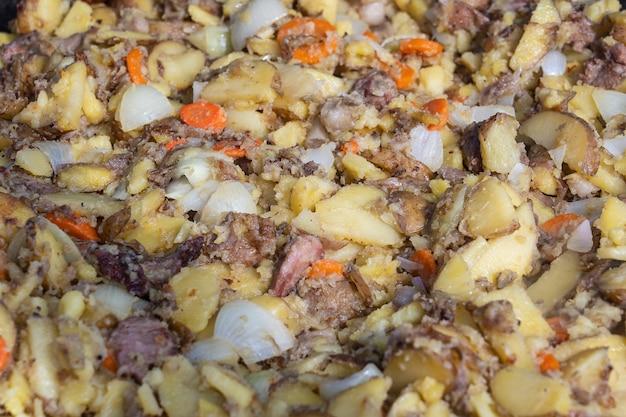 Rôtir les pommes de terre, les carottes, les oignons et la viande dans une grande poêle. nourriture délicieuse au festival. cuisine de campagne au foyer. les jeunes pommes de terre sont frites dans l'huile, la nourriture de rue, l'ukraine