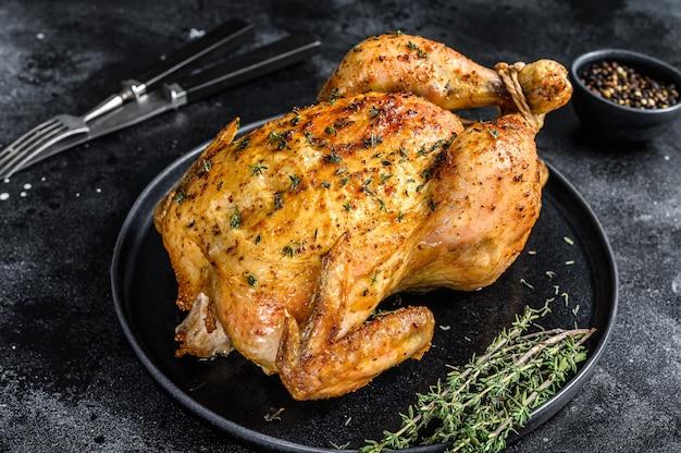 Rôtissoire de poulet entier cuit maison au thym.