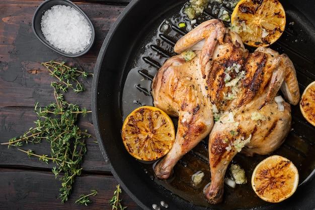 Rôtissoire de poulet maison au thym et au citron, sur une vieille table en bois, vue de dessus