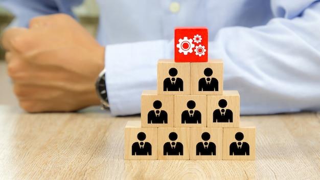 Rouage avec l'icône de personnes sur des blocs de jouets en bois cube empilés en forme de pyramide
