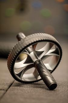 Roue abdominale utilisée pour exercer les muscles abdominaux. rouleau d'exercice de remise en forme d'entraînement sur sol noir dans la salle de gym.