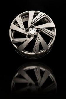 Roue en alliage gros plan sur un mur noir. couleur et réflexion de la roue grise, photo verticale.
