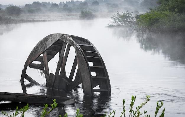 Une roue d'un ancien moulin à eau sur la rivière. le petit matin sur la rivière était couvert de brouillard.