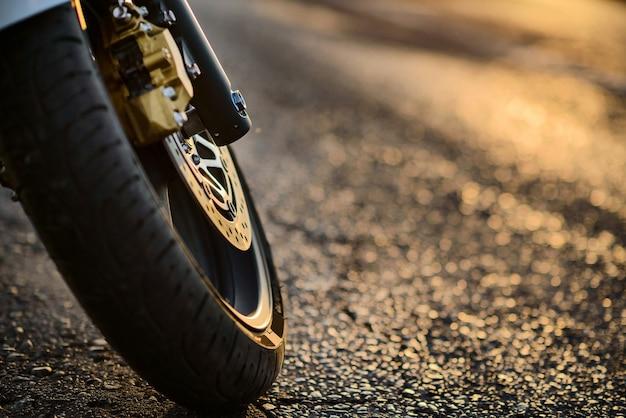 La roue avant d'une moto en gros plan dans les rayons du coucher du soleil.
