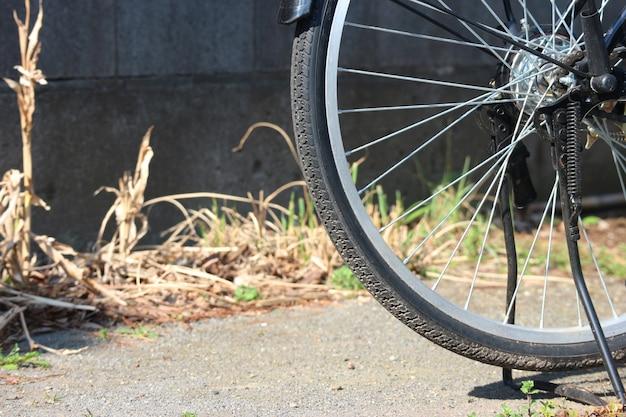 Roue de bicyclette de stationnement sur le fond de la route de ciment.