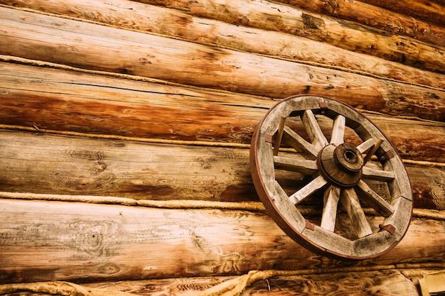 Roue en bois sur le mur de la maison en rondins