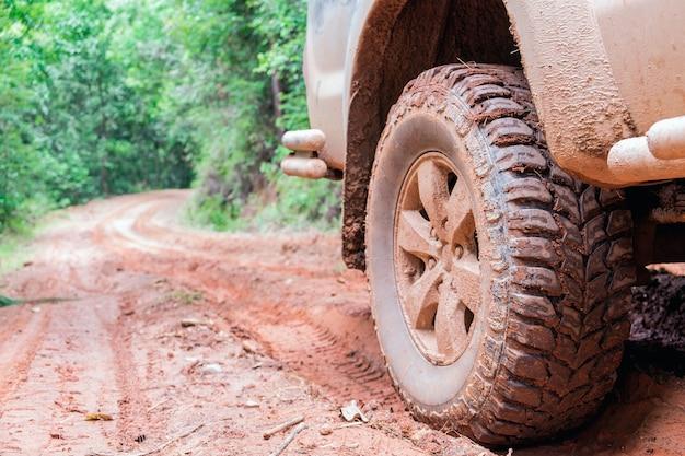 Roue closeup dans un paysage de campagne avec une route boueuse